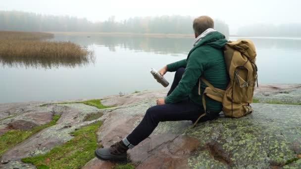 ein Mann mittleren Alters mit Rucksack sitzt an einem felsigen Ostseestrand.