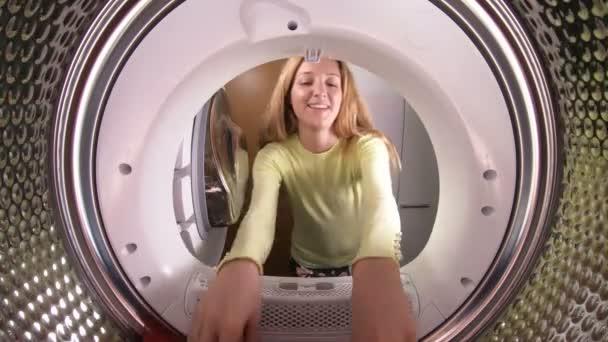 Vicces kis lány anyja és apja a ruhákat, hogy mosógéppel rakodási.