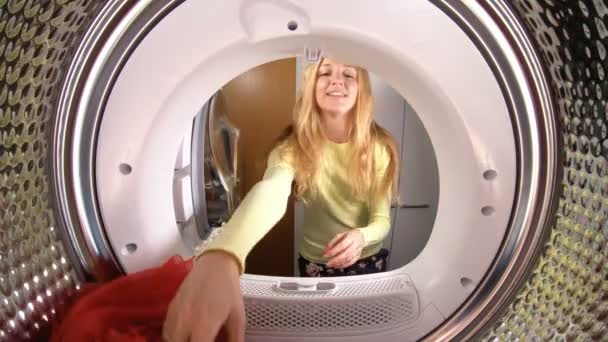 Funny little girl, her mother and father loading the their clothes and toys to washing machine. View from the inside of washing machine. Slow motion