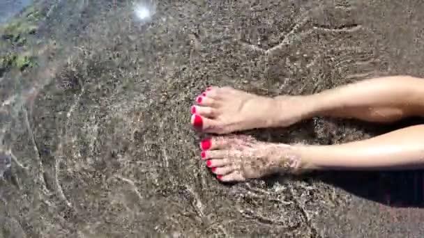 Womens piedi nelle onde del mare sulla spiaggia. Vista superiore della parte del corpo. Dita del piede di pedicure.