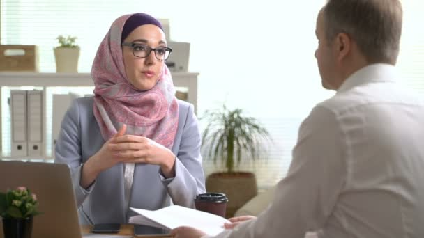 Young muslim business woman shake hands with a caucasian man during a meeting in office