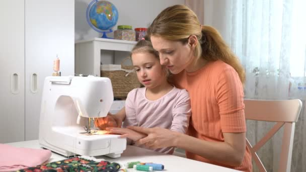 Mom teaching her little daughter to sew using a sewing machine in the nursery at home