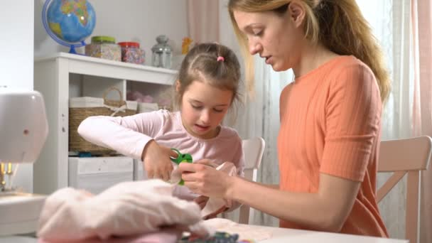 Mom and her little daughter do needlework together. Girl with scissors cuts the cloth for DIY