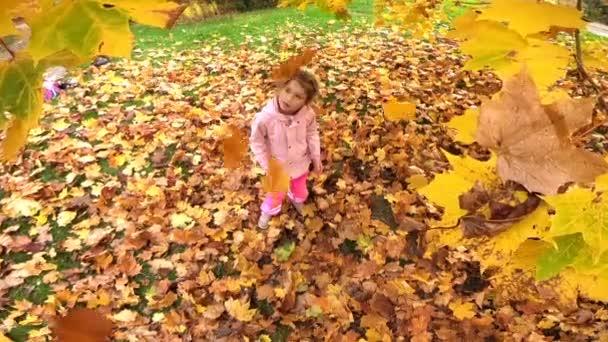 Kleines lachendes hübsches Mädchen wirft gelbe Blätter in Herbstpark