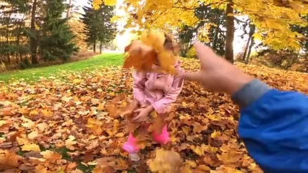 kis nevető csinos lány dob sárga levelek ősszel parkban