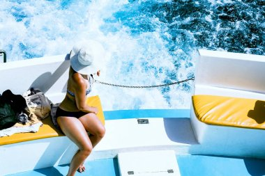 A girl in a hat rides a yacht and looking at the rolling waves. Cyprus, blue lagoon