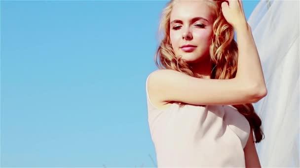 Egy gyönyörű szőke gondtalan lány áll a mezőn egy napsütéses napon, és egyenesíti a haját a szélben a háttér fehér átlátszó szövet, hogy a szél fúj. Lassú mozgás.