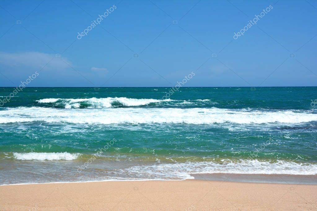 Beautiful tropical beach. Waves with crests breaking on the coas