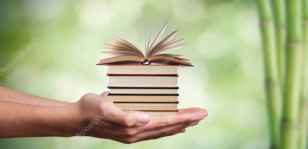 hands with stacked books and natural green background