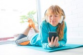 woman in sportswear listening to music with phone and headphones