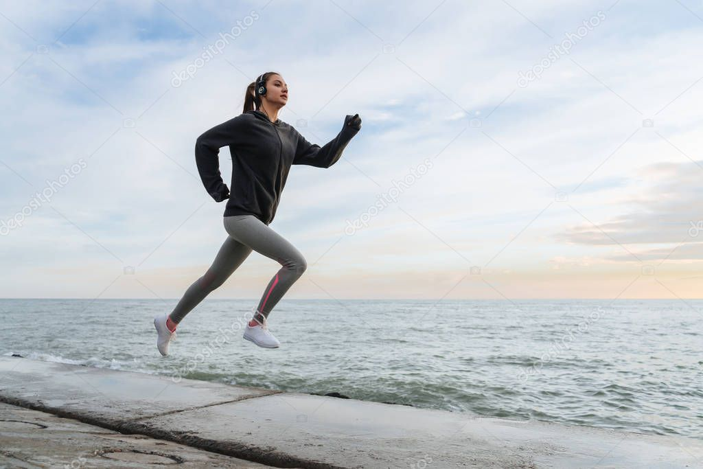 sports strong young girl jogging by the sea, preparing for competitions, listening to music on headphones