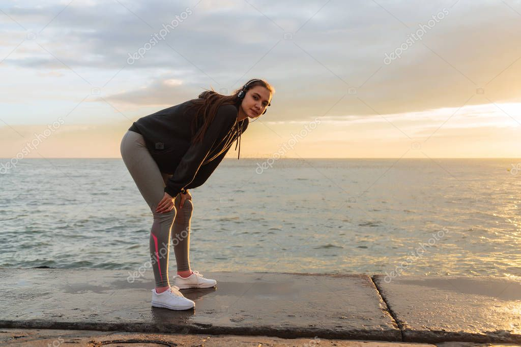 a cute young girl in sportswear jumped out by the sea at sunset, listening to music on headphones