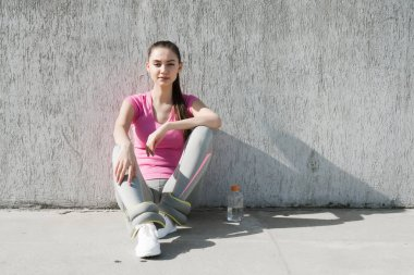 slender young girl sitting on the ground outdoors, gaining strength before training and drinking water