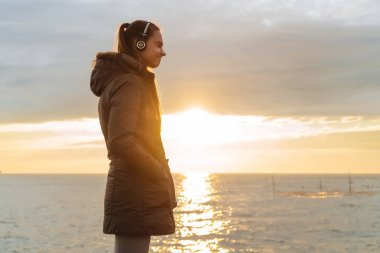 peaceful happy girl walks by the sea at sunset and listens to music on headphones