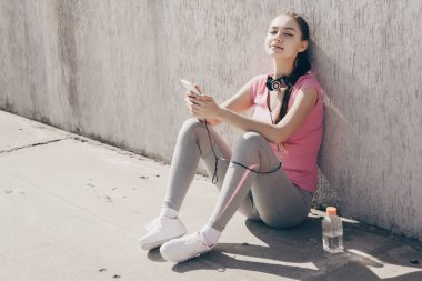 calm young girl in sportswear sits on the ground outdoors, resting and listening to music on headphones