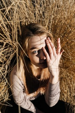 funny blue-eyed girl blonde sits in the field, closes her eyes from the sun