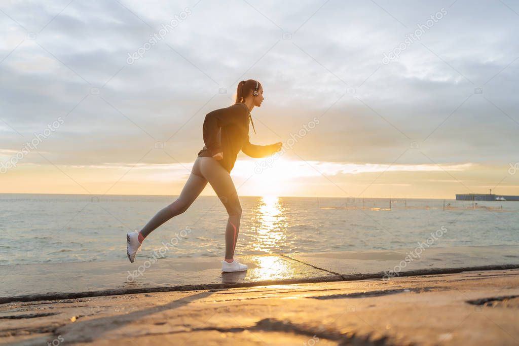 confident fast girl jogging by the sea at sunset, listening to music on headphones