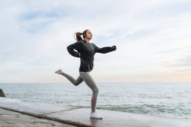 active athletic girl jogging by the sea, listening to music on headphones