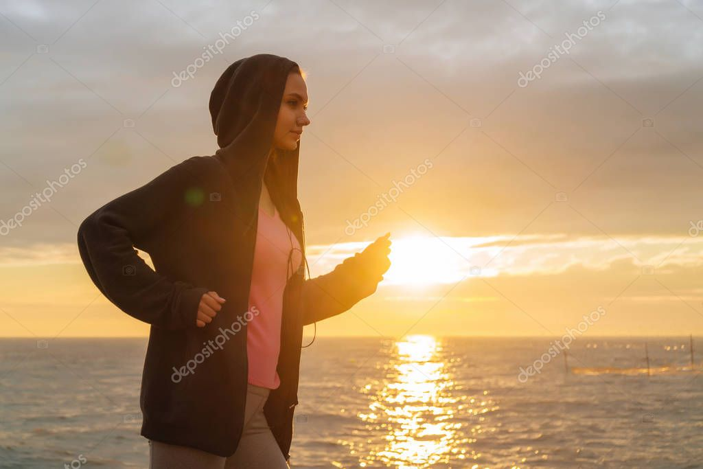 active young girl runner jogging by the sea at sunset, preparing for competitions