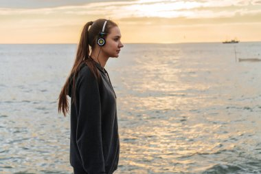 beautiful long-haired girl went for a run to the sea promenade in the evening, listens to music on headphones