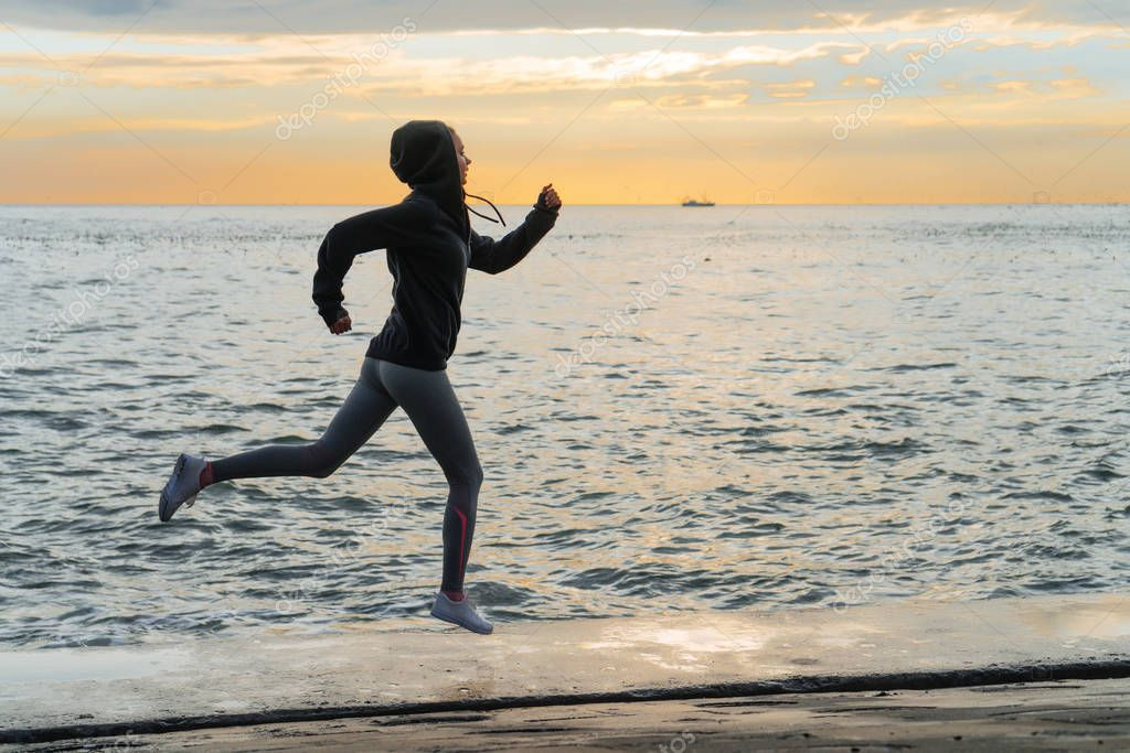 fast slender girl runner jogging by the sea in the evening, preparing for competitions