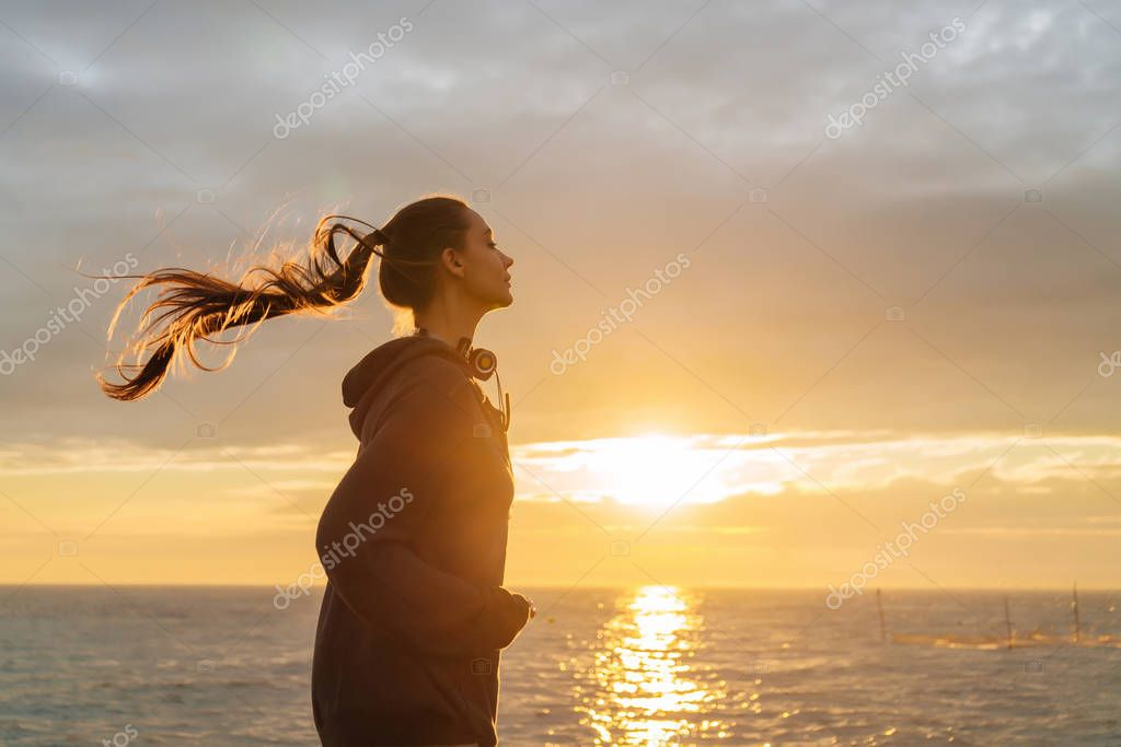 active long-haired girl sportswoman running around the seaside at sunset, getting ready for competitions