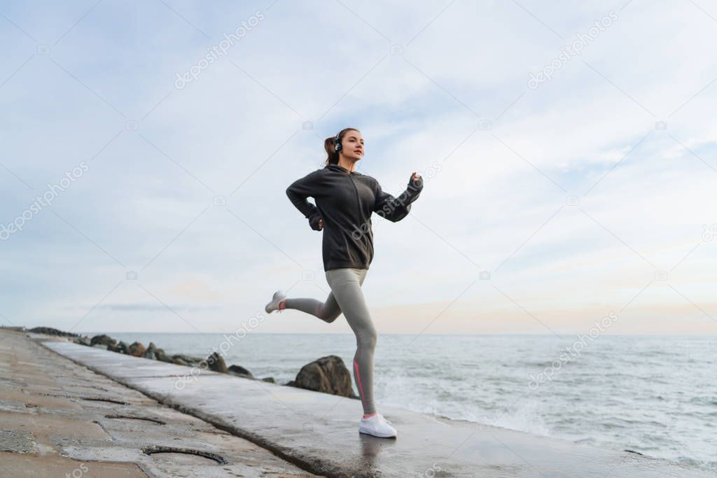 fast sports girl jogging by the sea, listening to music on headphones