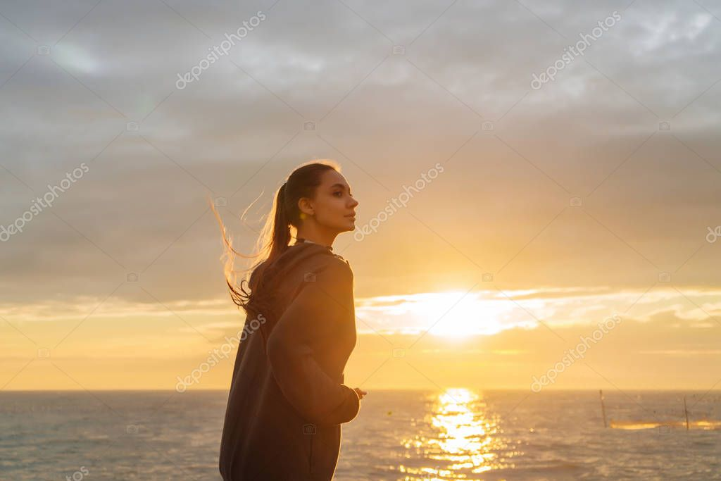 active long-haired girl runs at sunset by the sea, preparing for competitions