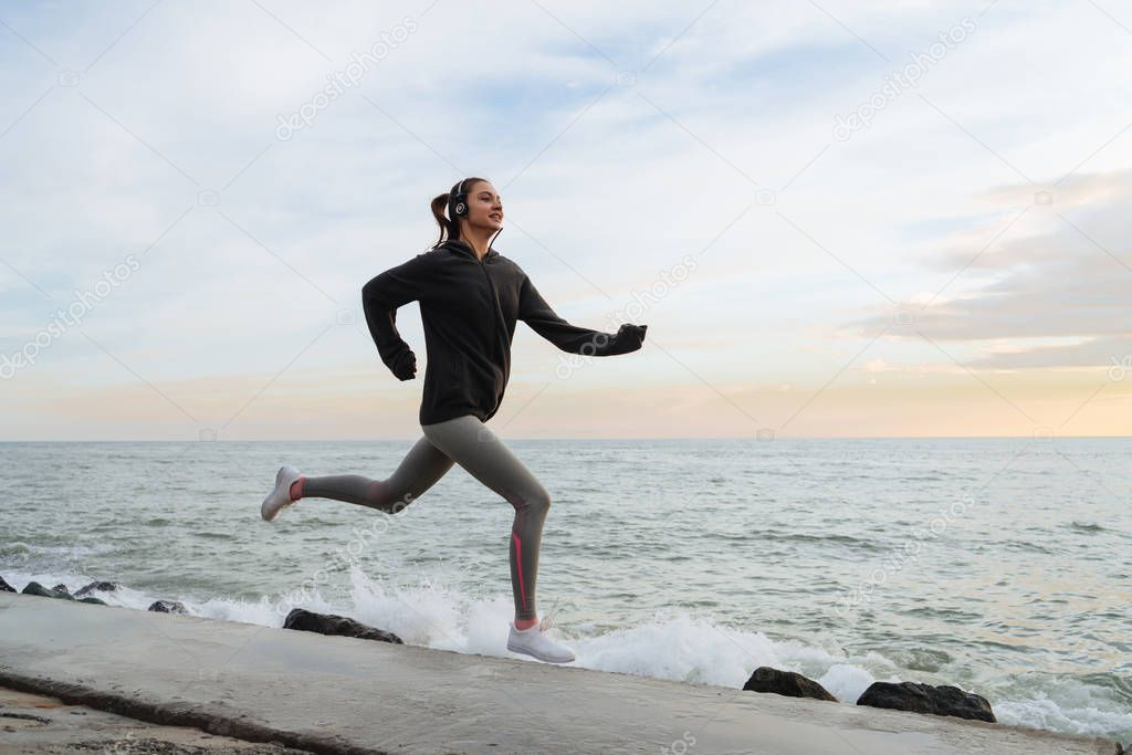 fast slender girl runs by the sea, listens to music on headphones, wants to lose weight
