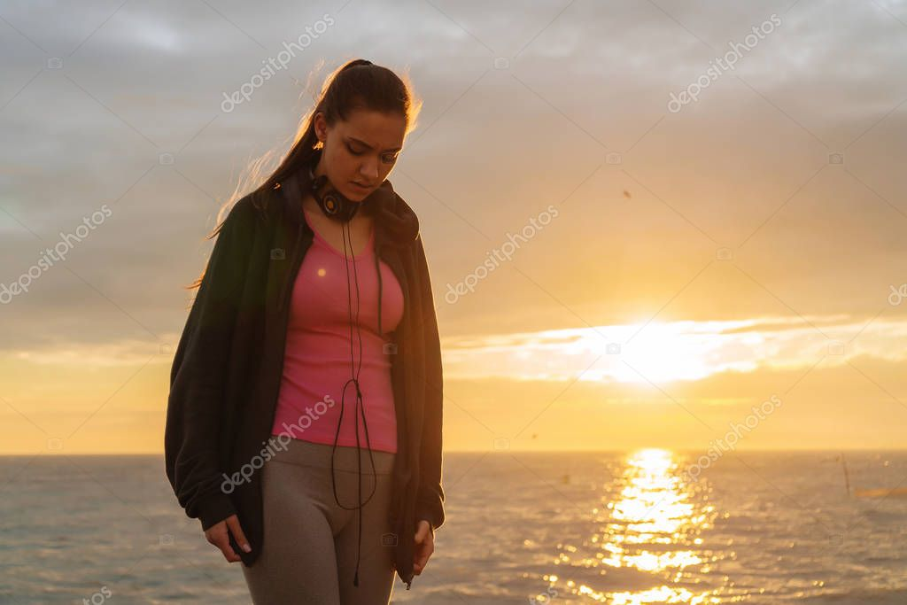 confident young girl resting after jogging in the evening by the sea, preparing for competitions on the run