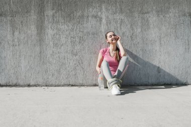 cute girl in a pink t-shirt is sitting on the ground, resting after a long run, smiling