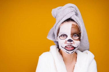 a funny young girl in a white coat, a towel on her head, a moisturizing mask with a dog's face on her face