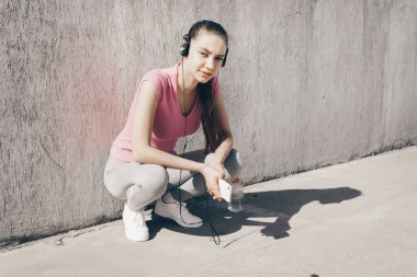 confident slender girl in a pink T-shirt listening to music on headphones, gaining strength before training