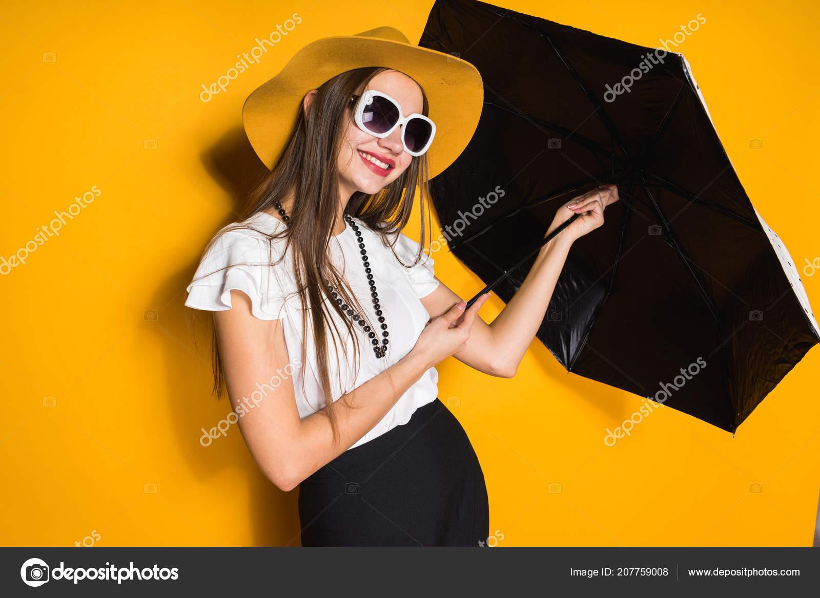 a36d705edb Χαμογελώντας αυτοπεποίθηση μακρυμάλλης κορίτσι μοντέλο στο καπέλο και γυαλιά  ηλίου κρατά ομπρέλα και θέτοντας σε κίτρινο φόντο — Εικόνα από ...