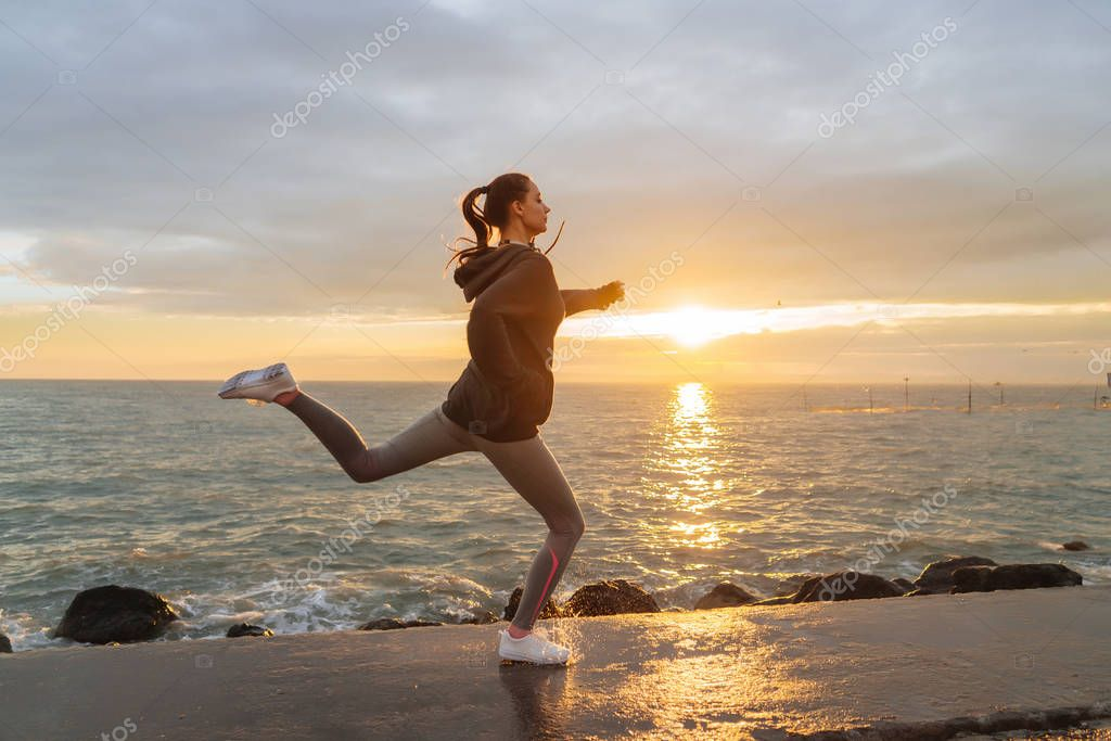active fast girl in sports clothes runs along the sea embankment at sunset, listens to music on headphones
