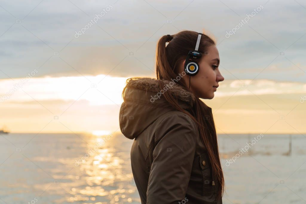 young beautiful girl in a warm jacket walking by the sea at sunset, listening to music on headphones