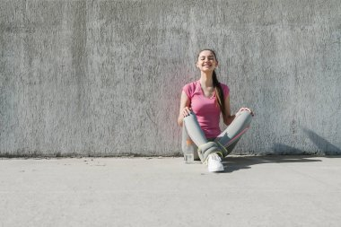 slender beautiful girl in a pink T-shirt is sitting on the ground outdoors, resting after jogging