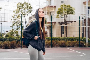 confident slender girl in a black sweatshirt with a hood holds a backpack, resting after training on the sports field