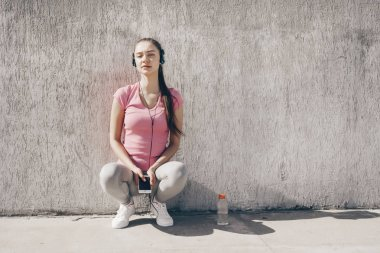 peaceful woman in a pink t-shirt resting after jogging, listening to music on headphones
