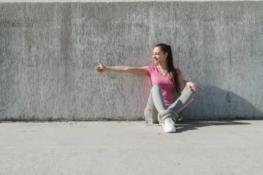 slender young girl in a pink t-shirt resting after a workout outdoors, sitting on the ground