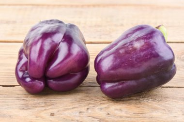 Two fresh purple bell peppers on a wooden table.