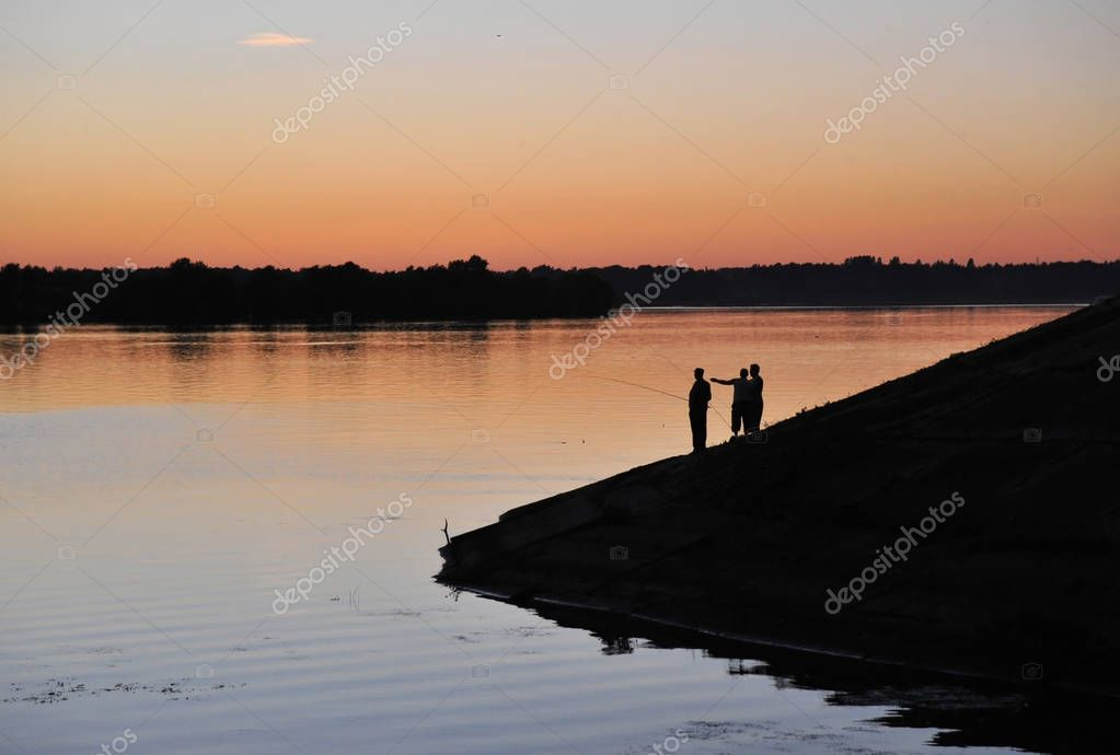 Silhouettes of fishermen on the banks of the Volga River in Uglich.