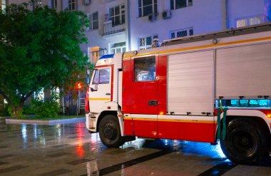 Yangının çıktığı apartmanın bahçesindeki itfaiye arabaları, yağmurun yağdığı gece..
