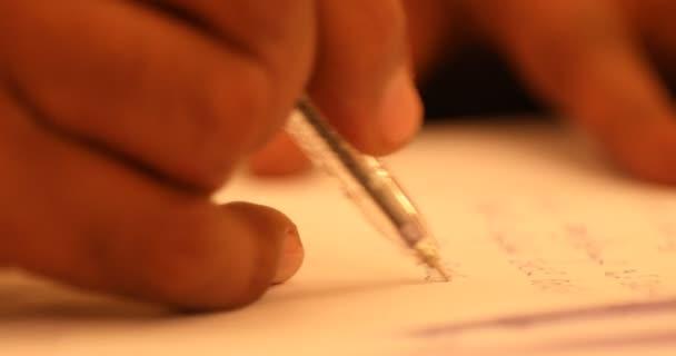 Mužská ruka s perem a papíry