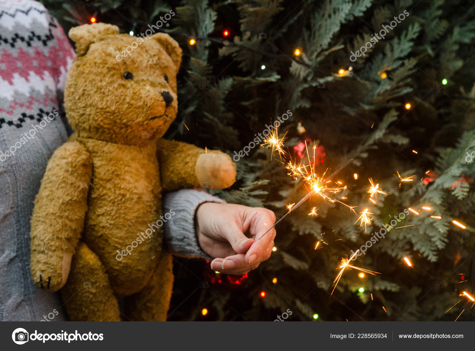 b73ec1ef82 Christmas scene - woman in knitted sweater holding an old teddy bear and  sparkler before christmas tree– stock image
