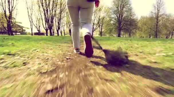Dívka prochází lesem s plastovým pytlem, který jí visel na noze.