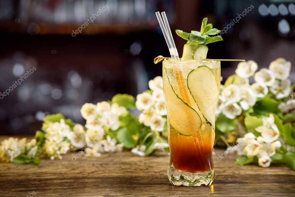 summer cocktail with cucumber on a wooden table on a floral background