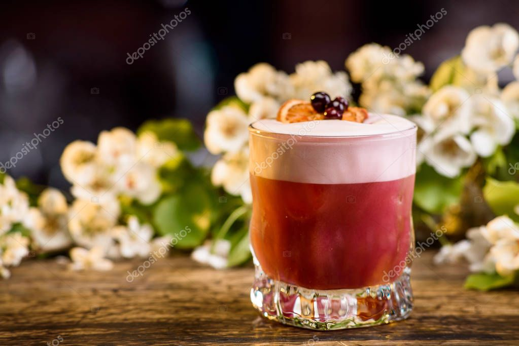 summer cocktail in layers, decorated with a berry and an orange slice. on a flowers background