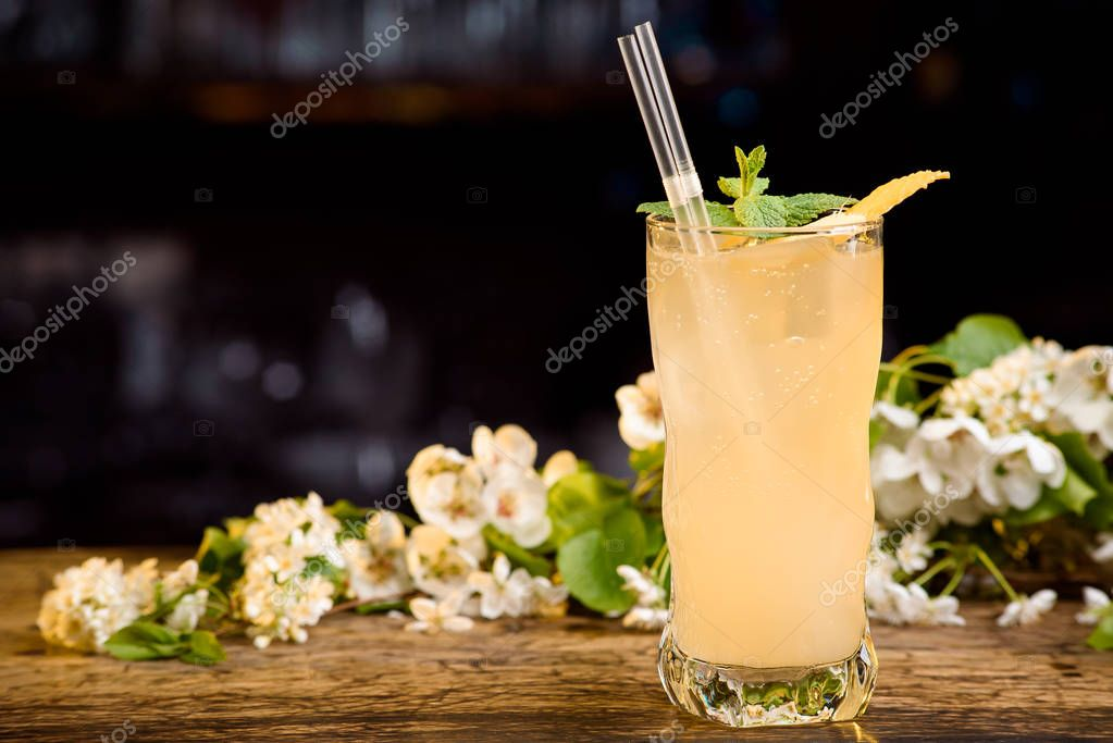 yellow summer cocktail decorated with mint and lemon rind on a wooden table on a floral background