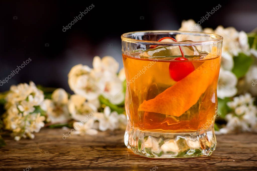 cocktail with whiskey and orange peel on a bar counter on a floral background